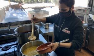 Una cuinera prepara una ració d'escudella per servir-la.