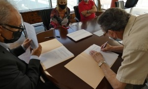El pintor Galobardes signant la cessió, amb el cònsol Francesc Camp i familiars de l'artista.
