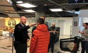 La seguretat de Pyrénnés pren la temperatura a un client abans d'entrar al supermercat.