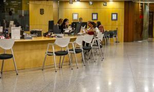 Treballadors públics atenent ciutadans al servei de Tràmits de l'edifici administratiu del Govern.