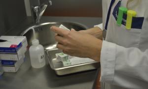 Un professional mèdic prepara medicaments abans d'atendre un pacient.
