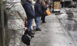 Usuaris del transport públic, entre els quals esquiadors, esperant l'arribada de l'autobús.