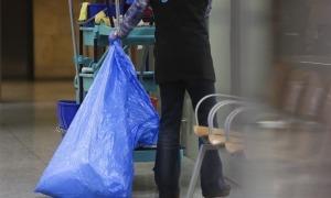 Una dona realitzant tasques de neteja al seu lloc de treball.