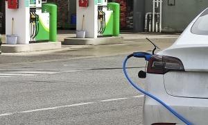 Un vehicle elèctric carregant-se en una zona propera a una estació de servei.