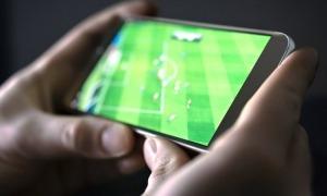 Un usuari segueix un partit a través d'una aplicació mòbil.