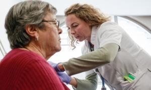 La infermera Patricia López administra les primeres dosis de la vacuna de la grip.