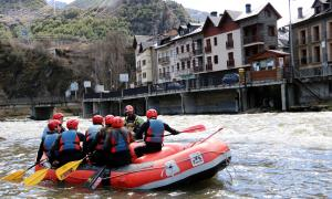 Una barca de ràfting amb clients i el poble de Llavorsí (Pallars Sobirà) al fons.