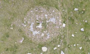 Vista aèria del dolmen d'Encenrera: les lloses de la cambra mortuòria, al centre del túmul, són quasi tan llargues com el pal, que fa dos metres.
