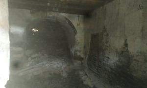Inquietant estat de l'interior de la capella, amb el terra enfonsat i un forat al mur de l'absis.