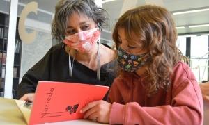 Mar Garcia i una joveníssima escolar de Fígols, Mali, examinen un dels exemplars del facsímil de 'Narieda'.