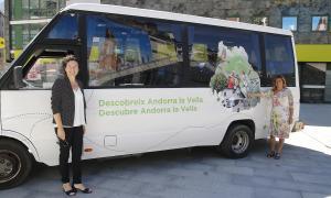 Mònica Codina i Eva Roma mostrant l'autobús que farà els trasllats a les dues valls, ahir.