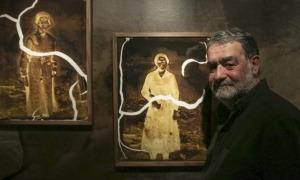 El fotògraf català posa davant dues de les fotografies que va esporgar a l'Arxiu Nacional.