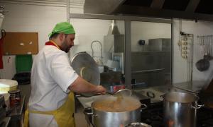 Un cuiner a l'institut Joan Brudieu fent un dels plats del projecte 'Mengem d'aquí'.
