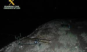 Una canya de pescar instal·lada de nit en un embassament.
