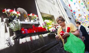 Una veïna encèn una espelma a l'oratori de Sant Antoni, al Puial.