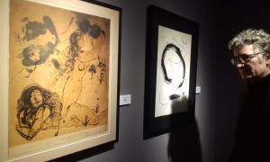 Jordi Obiols contempla un dibuix de MIró i un altre de Dalí, dues de les obres que s'exposen al Museu Fàbrica Reig.