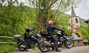 Dos motoristes mirant l'ermita d'Unarre, al Pallars Sobirà.
