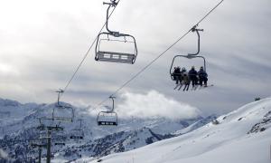 Esquiadors pujant amb un telecadira a l'estació aranesa de Baqueira Beret.