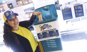 Una resident veneçolana fa la seva aportació al contenidor instal·lat a La Llacuna.