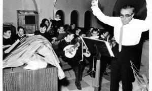 El mestre Joan Serra, que exercia com a professor a l'escola espanyola, dirigeix un assaig de la tuna a Sant Esteve; entre els tuners hi ha els germans Jordi i Josep Maria Tejero, Virgili Tomàs, Enric Bartumeu, Joan lladós i Toni Portell, entre d'altres.