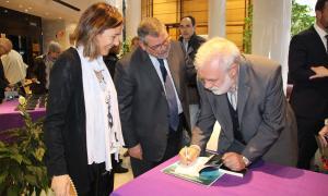 Dalleres firma un exemplar del llibre davant de la cònsol menor, Ester París, i el president del consell d'administració de la CASS, Jean Michel Rascagneres.