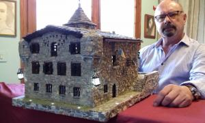 Joaquim Bessa Macedo, al seu pis-taller de la capital, amb la maqueta de Casa de la Vall, l'última que ha construït, d'un detallisme extrem que inclou estripagecs, porticons, escut, bandera i rodes de molí.