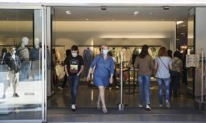 Clients amb mascareta surten d'un comerç de moda de la capital.