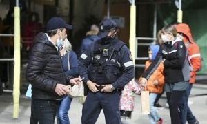 Un agent de policia informa un turista que no pot fumar i estar sense mascareta al mig del carrer.