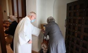 Mossèn Ramon ajuda una feligresa a servir-se gel desinfectant a l'entrada a missa de 12.