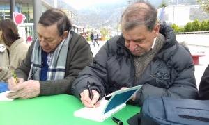 Antoni Morell i Robert Pastor firmen exemplars a la plaça del Poble, a la diada del llibre de l'any passat.