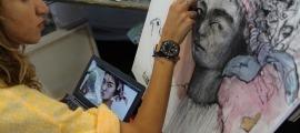 Una de les artistes de l'Art Camp treballant en un dels seus quadres.