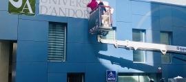 Uns operaris instal·len la retolació exterior de l'edifici Cub de la Universitat d'Andorra.
