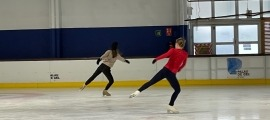Czisny mostrant a una jove patinadora un moviment.