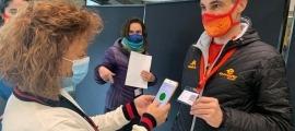 Un dels participants mostra el seu forfet sanitari en el punt de control.