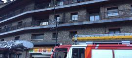 Un camió de bombers davant de l'edifici on s'ha cremant el pis.