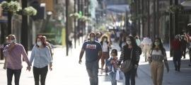 Gent amb mascareta caminant per l'avinguda Meritxell.
