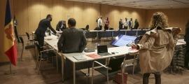 Instants previs a l'inici de la Taula Nacional de l'Habitatge amb el ministre d'Ordenament Territorial, Jordi Torres, saltant per damunt la taula per endollar uns cables, aquest dilluns.