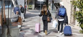 Dos turistes amb maletes pel centre d'Escaldes-Engordany.