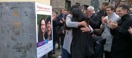 """Olga Molné i Eva Sansa s'abracen després de penjar el primer cartell i donar el tret d'inici a la campanya d'uns comicis """"una mica especials""""."""