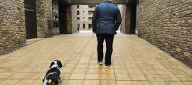 Un home entra amb un gos cap a un habitatge.