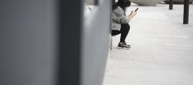 Una persona utilitzant el seu telèfon mòbil.