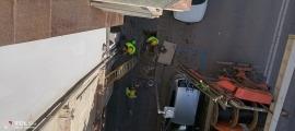Vista dels operaris de Peusa treballant per impedir l'accés fraudulent al subministrament, des d'un dels pisos ocupats.