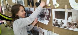Una nena penjant una fotografia en un mural.