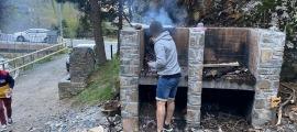 Un dels joves preparant el foc de la barbacoa diumenge a la tarda.