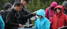 Els participants a la carrera d'orientació consulten el mapa abans de la sortida.