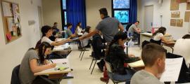 Un professor reparteix les proves de l'examen oficial de batxillerat.