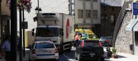 El camió estacionat al costat esquerre de la calçada i el vianant sortint de l'ambulància, en el lloc dels fets.